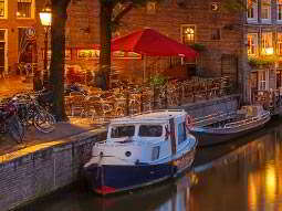 Two boats moored by the canal, with a seating area and some bikes parked