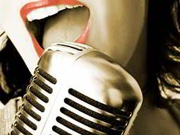 Close up of a womans mouth singing into a mic