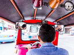 Close up on the back of a man sat in a tuk tuk