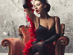 A woman with a feather boa around her, on a red, leather chair