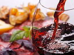 A glass of red wine being poured with some meat in the background