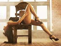 A semi naked woman lying backwards on a chair