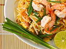 Close up of thai noodles and prawns on a white plate