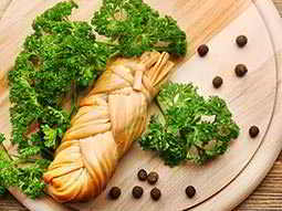 Close up of a baguette on a wooden board, served alongside green leaves