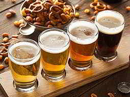 Four glasses of beer in a wooden rack surrounded by bar snacks