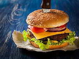 A burger with a knife in the middle of it