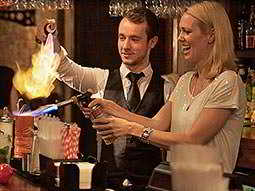 A man and a woman using a blow torch to set a cocktail on fire