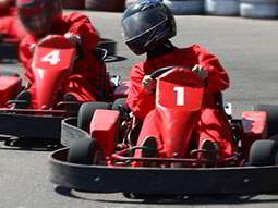 Three red go karts whizzing around a track