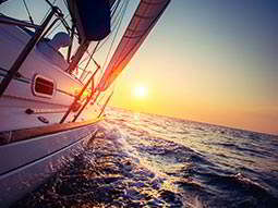 The side of a catamaran sailing on the sea at sunset
