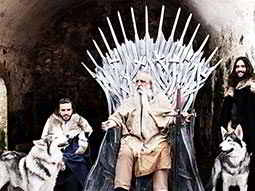 A man in costume sat on the Iron Throne from Game of Thrones, with two people sat next to him
