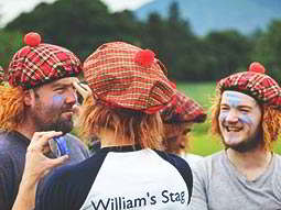 A group of men wearing tartan hats with wigs and blue face paint