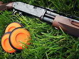 Three orange clays and a gun lying in a field