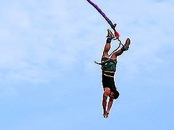 A man falls vertically, with a bungee cord attached to his legs