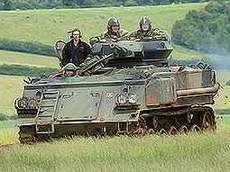 Some people driving a tank in a field