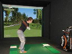 A man swinging a golf club in a virtual golf booth
