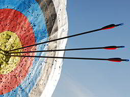 Three arrows in the bullseye of a red, black, yellow and white target