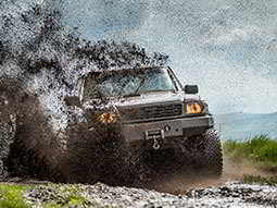 A 4x4 driving through a puddle of mud