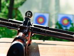 Close up of a crossbow on a table, with blurred targets in the background