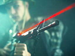 A red laser beam from a laser gun, with a blurred man holding it in camouflage gear