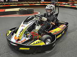 A man driving a go kart around a corner of a track
