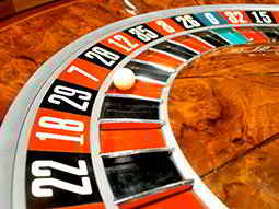 A roulette wheel with the ball landing on red seven