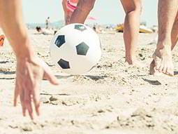 A ball bouncing on the beach with peoples hands near it