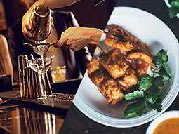 A split image of a cocktail being double strained into a glass on a bar top and a plate of meat on skewers