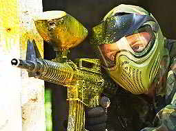 A man wearing a full-face paintball mask and camouflage overalls aims a paintball gun covered in yellow paint