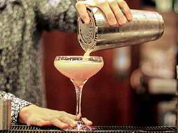 A womans hand pouring out a woman pale pink cocktail into a martini glass