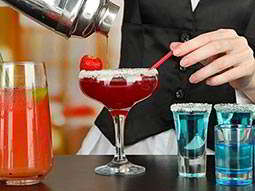 A dark red cocktail being strained into a coupe glass, with other drinks nearby