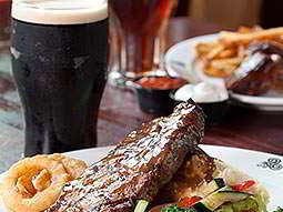 A steak meal next to a pint of Guinness, with more food and drink in the background