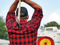 A man preparing to throw a large axe at a red and yellow target