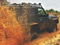 A 4x4 vehicle with its rear wheels bogged down, spraying orange muddy water out behind it