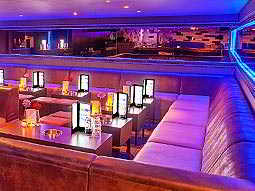 A lounge-style seating area at a bar, with purple and blue lighting