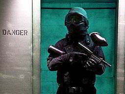 A man in a black jacket and green helmet standing in a doorway, whilst holding a paintball gun