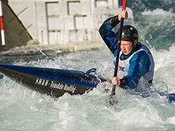 A man paddling a black kayak through rolling rapids