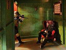A man in a paintball mask standing and aiming a paintball gun at another man slumped in a red chair