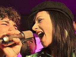Man and woman singing into a mic