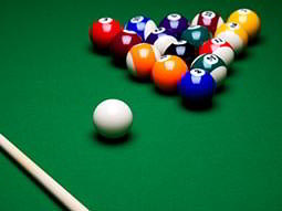 A racked set of pool balls, a cue ball and a cue on a green pool table