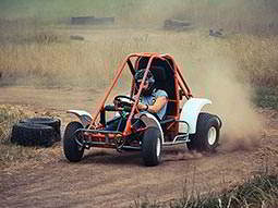 A man driving a off-road buggy round a corner on a dirt track