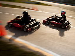 Two people in helmets and overalls, racing on an outdoor track