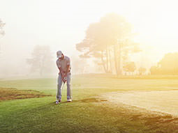 A man playing golf on the golfing green