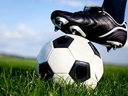 Close up of a black football boot on top of a black and white football, on grass