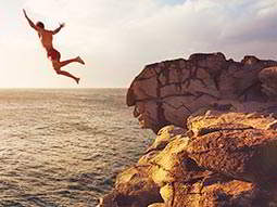 A man jumping off a cliff into the sea