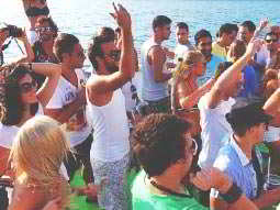Some young people on a party boat, with the sea in the background