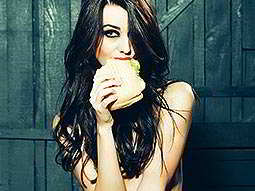 A naked woman eating a sandwich