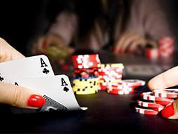 A woman's hands lifting two playing cards, with poker chips and another person in the background
