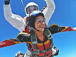 A man and woman doing a tandem skydive with a blue sky in the background