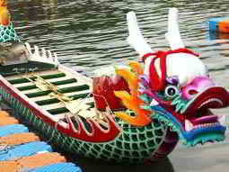 A colourful dragon boat, with paddles on the benches, on a river