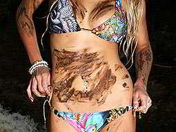A womans body in a colourful bikini with mud on the stomach